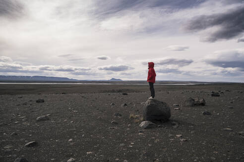 Young woman standing on a rock in the volcanic highlands of Iceland - UUF18781