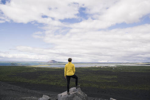 Young woman standing on Hverfjall crater near Myvatn, Iceland, looking at view - UUF18784
