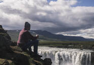 Mann sitting with a cup of coffee, looking at Godafoss waterfalls, Iceland - UUF18793