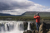 Man looking at Godafoss waterfalls, Iceland, with binoculars - UUF18796