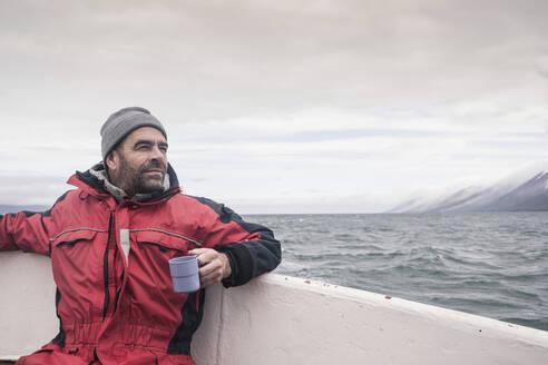 Mature man looking at the sea, boating on Eyjafjordur Fjord, Iceland - UUF18805