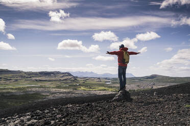Hiker in Vesturland, Iceland, standing with arms out and looking at landscape - UUF18814