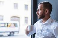 Businessman in office having a coffee break looking out of window - DIGF07912