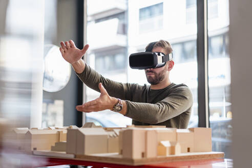 Man with architectural model in office wearing VR glasses - DIGF07915