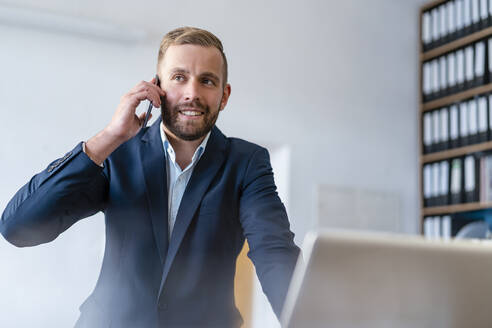 Smiling businessman on cell phone in office - DIGF07927