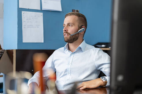 Businessman with headset at desk in office - DIGF07942