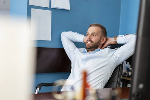 Smiling businessman leaning back at desk in office - DIGF07945