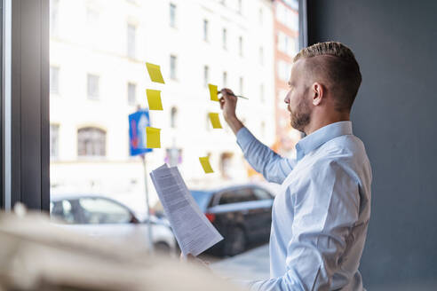 Businessman writing on adhesive notes at glass pane - DIGF07987