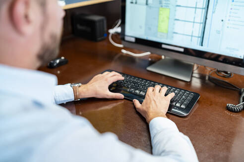 Close-up of businessman working on desktop pc in office - DIGF08002