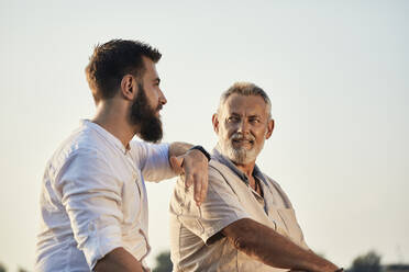 Father and adult son talking outdoors - ZEDF02532
