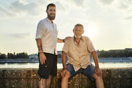 Portrait of smiling father and adult son at the riverside at sunset - ZEDF02535