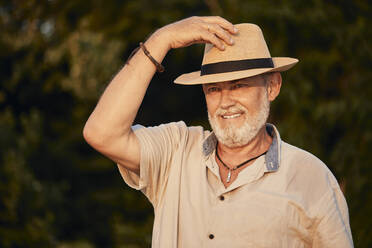 Portrait of a smiling senior man wearing summer hat outdoors - ZEDF02544