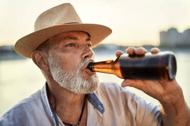 Senior man drinking a beer at the riverside at sunset - ZEDF02550