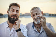 Portrait of smiling father and adult son scratching their beards - ZEDF02553