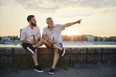 Father and adult son sitting on a wall at the riverside at sunset drinking a beer - ZEDF02556