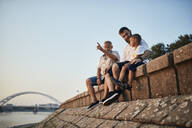 Grandfather, father and son sitting on a wall at the riverside - ZEDF02559