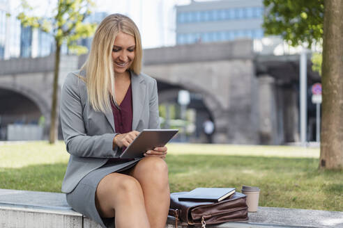 Smiling blond businesswoman sitting on a wall outdoors using digital tablet - DIGF08012