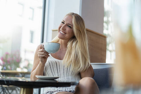 Portrait of happy blond woman drinking coffee in a cafe - DIGF08018