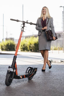 Portrait of happy businesswoman with electric scooter - DIGF08030