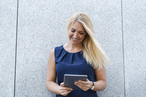 Portrait of smiling blond businesswoman looking at digital tablet - DIGF08048