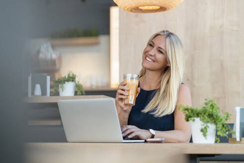 Portrait of smiling blond businesswoman with laptop and glass of orange juice in a coffee shop - DIGF08054