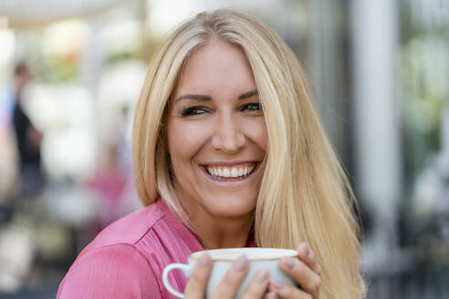 Portrait of happy blond woman with cup of coffee - DIGF08060