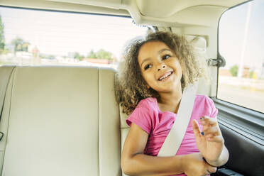 Mixed race girl smiling in back seat of car - BLEF14291