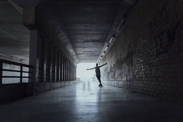 Silhouette of young man with longboard in a tunnel - AFVF03790