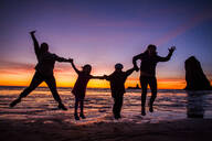 Silhouette of Caucasian family jumping for joy on Cannon Beach, Oregon, United States - BLEF14357