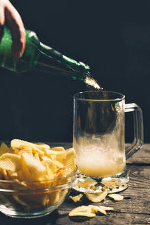 Hand pouring glass of beer near potato chips - BLEF14420