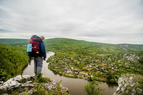 Caucasian hiker admiring scenic view of village - BLEF14456
