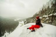Caucasian hiker sitting on snowy hilltop - BLEF14462