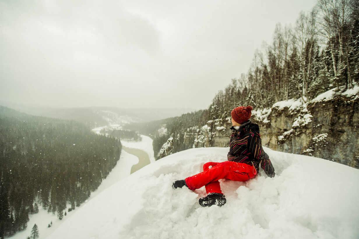 Caucasian hiker sitting on snowy hilltop - BLEF14462 - Aleksander Rubtsov/Westend61