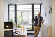 Caucasian businessman talking on cell phone in office - BLEF14504