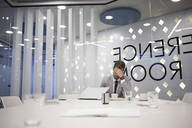 Caucasian businessman working in conference room - BLEF14513