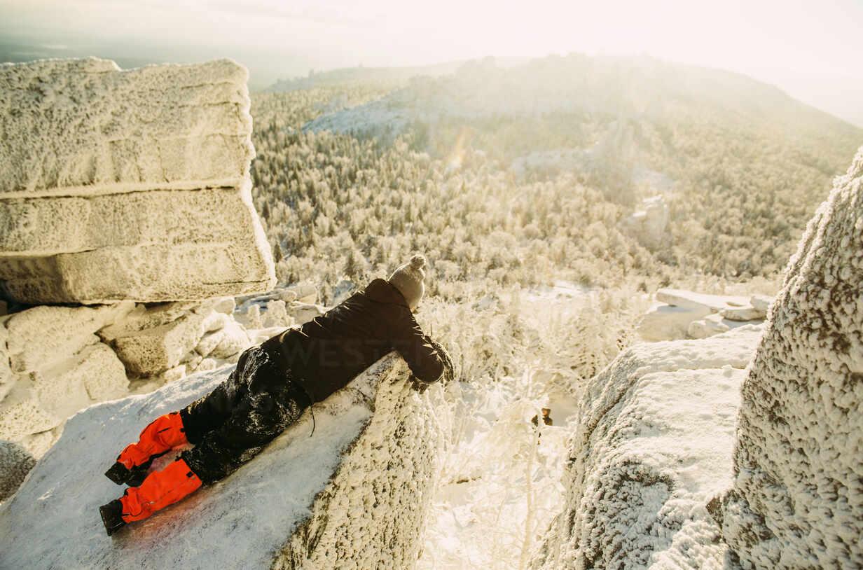 Caucasian hiker laying on snowy rock formations - BLEF14546 - Aleksander Rubtsov/Westend61