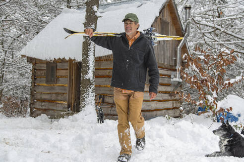 Mixed race man carrying skis near snowy shed - BLEF14558