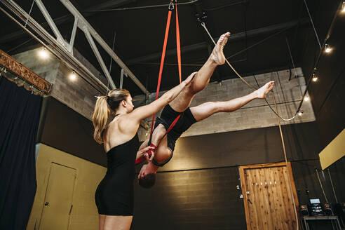 Caucasian acrobats training on ropes in studio - BLEF14588