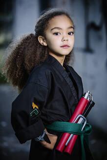Mixed race girl wearing martial arts uniform with nunchucks - BLEF14600