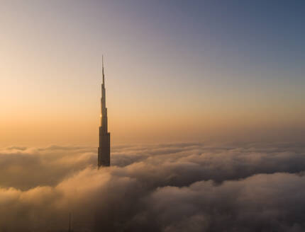 Aerial view of Burj Khalifa Tower in a sea of clouds at sunset in Dubai, United Arab Emirates. - AAEF01754
