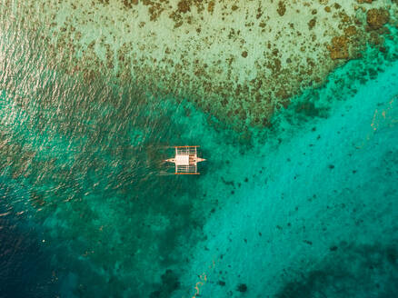 Aerial view of traditional filipino fishing boat by Sumilon island, Philippines. - AAEF01790