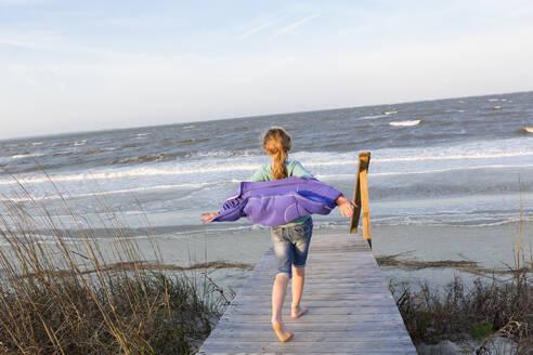 Caucasian girl walking on wooden walkway to beach - BLEF14669