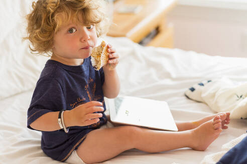 Caucasian baby boy eating and using digital tablet on bed - BLEF14672