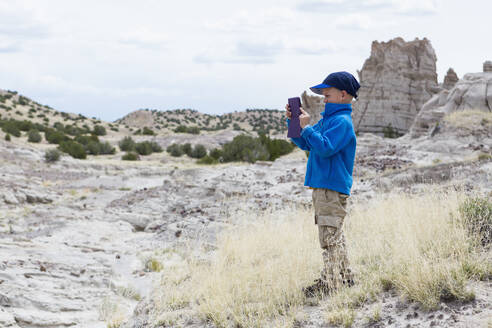 Boy photographing rock formations in desert landscape - BLEF14684