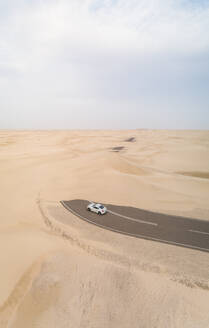 Aerial view of white car in road covered by sand in the desert, Abu Dhabi, UAE - AAEF02346