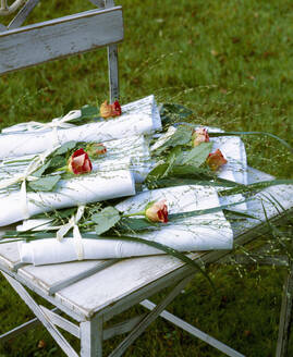 Close-up of decorated napkins with roses on wooden chair in back yard - PPXF00222
