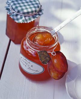 Homemade peach jam in mason jar on table - PPXF00231