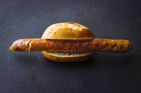 Roasted sausage in bread roll isolated on dark background - PPXF00234