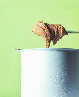 Chocolate ice cream in container during preparation against green background - PPXF00237