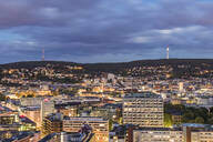 Illuminated buildings and communications tower against cloudy sky at dusk in Stuttgart, Germany - WDF05399